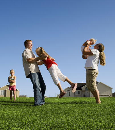 Family playing outside in the grass.
